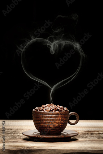 Wooden cup with beans and heart-shaped smoke