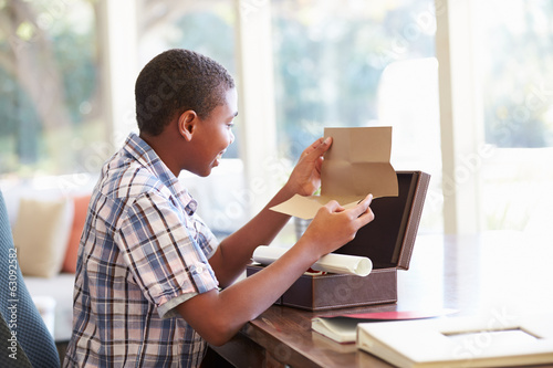 Boy Looking At Letter In Keepsake Box On Desk