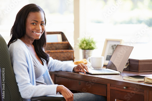 Woman Using Laptop On Desk At Home