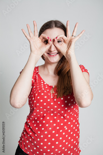 Smiling attractive woman looking through finger goggles