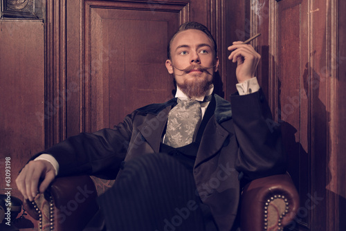 Vintage 1900 fashion man with beard. Sitting in old wooden readi - 63093198
