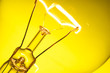Close up glowing light bulb on yellow background