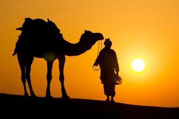 A desert local walks a camel through Thar Desert