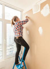 Slim woman working with putty and spatula on ladder