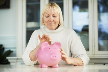 Old woman showing piggybank and euro coin