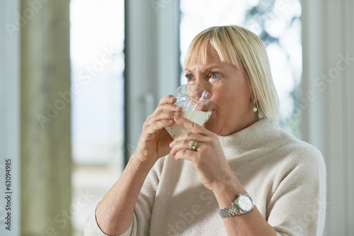 Portrait of senior woman having breakfast with milk