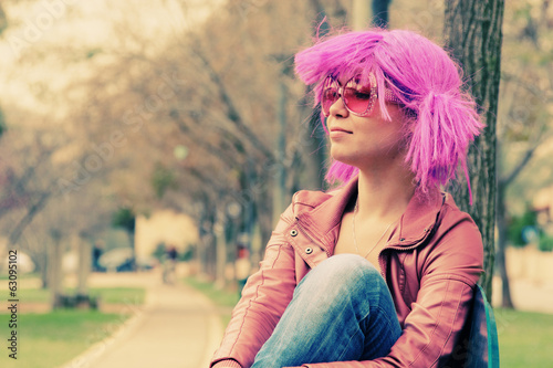 beautiful young woman with pink sunglasses and purple hair stand