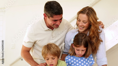 Happy parents and children drawing together looking at camera