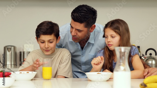 Father chatting with his children having breakfast