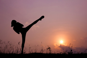 Silhouette of girl exercising side kick.