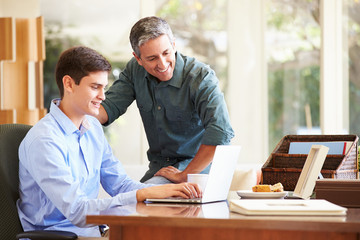 Father And Teenage Son Looking At Laptop Together