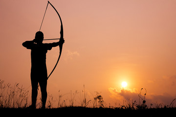 Silhouette archery shoots a bow