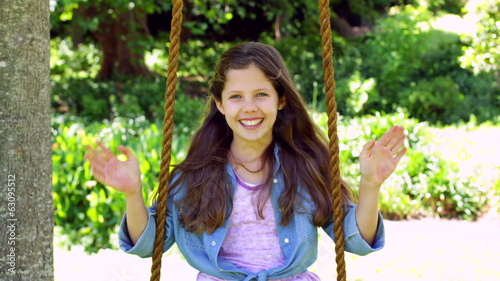 Smiling little girl sitting on a swing in the park