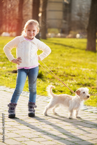 Little girl walking with her puppy dog in the park
