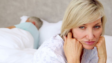 Unhappy woman thinking while her husband is sleeping