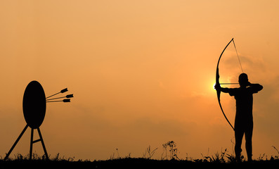 Silhouette archery shoots a bow at the target.