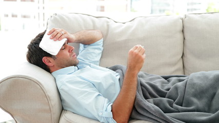 Man lying on the couch sick with a temperature