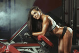 Fototapety Woman resting after lifting barbells