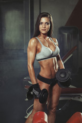 Woman with dumbbells in gym