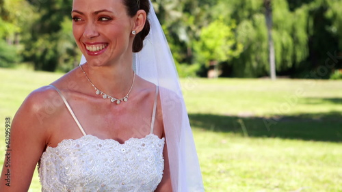 Smiling bride sitting on the grass