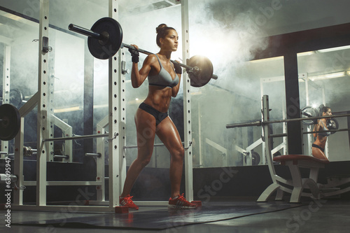 Woman lifting weight in gym - 63095947