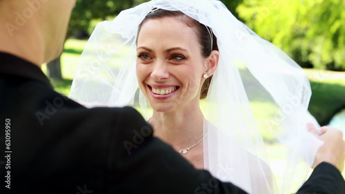 Groom lifting veil off beaming brides face