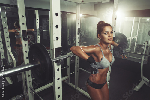 Woman resting after lifting barbells