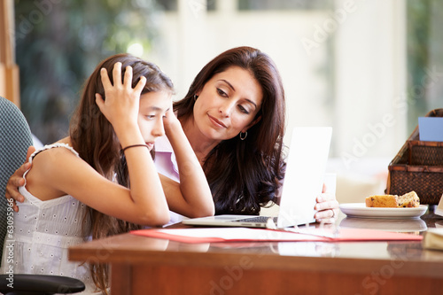 Mother Helping Stressed Teenage Daughter Looking At Laptop