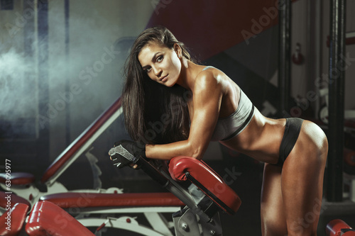 Woman resting after lifting barbells - 63095977