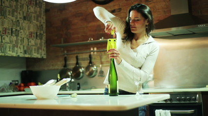 Young woman opening bottle of wine in her kitchen