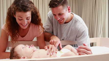 Happy parents playing with cute baby son in his crib