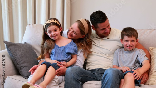 Happy young family sitting on sofa smiling at camera