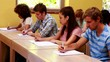 Focused students sitting in a line writing in classroom