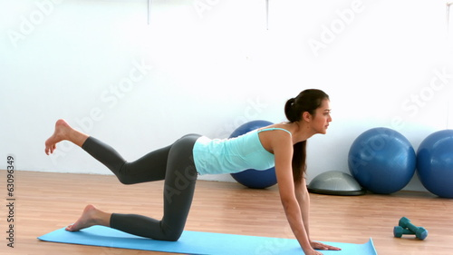 Fit brunette doing pilates move in studio