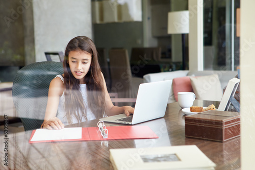 View Of Teenage Girl Using Laptop Through Window