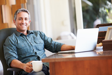 Mature Hispanic Man Using Laptop On Desk At Home