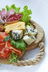 Italian cuisine. Prosciutto, cheese, salami, herbs.