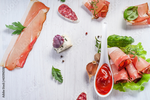 Sliced prosciutto in white wooden background