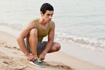 Young athletic man exercising and doing fitness
