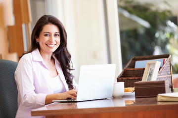 Hispanic Woman Using Laptop On Desk At Home
