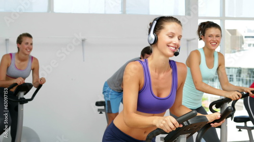Spinning class in fitness studio led by energetic instructor