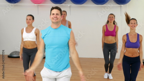 Aerobics instructor leading a happy class of women