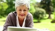 Happy senior woman relaxing in the park using her tablet
