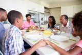 Multi-Generation Family Saying Prayer Before Eating Meal