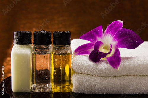 Spa setting with towels aroma oil bottles and orchid.