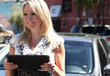 Pretty blonde woman with tablet in front of her car