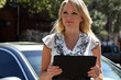 Businesswoman with tablet in front of her car in parking lot