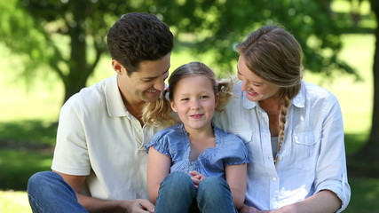 Happy parents with their young daughter in the park