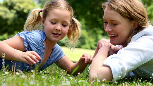 Happy mother lying on the grass with her little girl in the