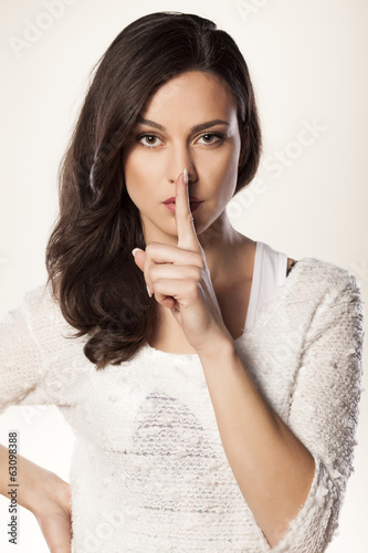serious girl holds a finger to her mouth